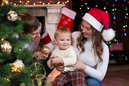fireplace living room: Happy family with child son decorating Christmas tree in front of fireplace  in living room Stock Photo