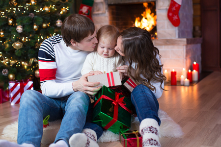 baby open present: Happy parents kissing child son and giving gifts on Christmas and New Year