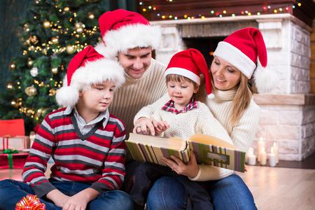 mujeres juntas: Familia revisar fotos en álbum juntos cerca del árbol de Navidad en frente de la chimenea