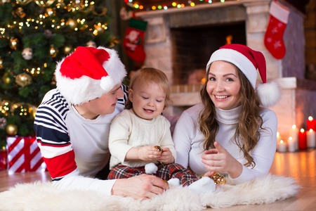 fireplace living room: Happy family playing with baby son lying near Christmas tree and fireplace  in living room