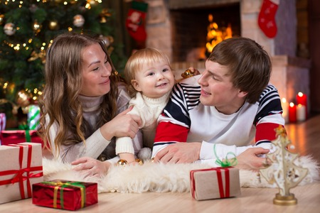 fireplace living room: Happy family with little son lying near Christmas tree and fireplace  in living room