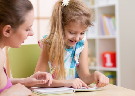 Mother teaching her kid daughter to read photo