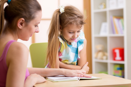 teacher student: Child Pupil Reading With Teacher In Elementary School Stock Photo