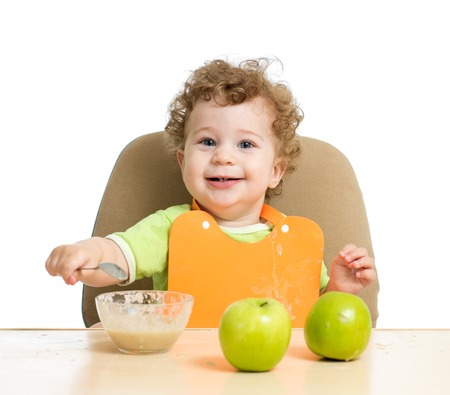 eating food: little child eats with spoon sitting at table with fruits isolated