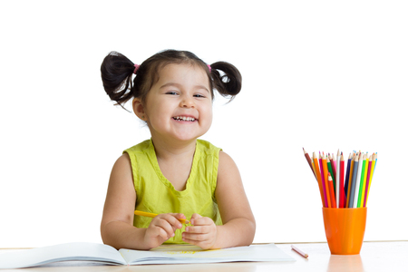 Cute child girl drawing with colorful crayons isolated on white