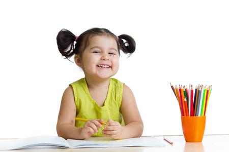 Mignon enfant fille dessin avec des crayons colorés isolé sur blanc
