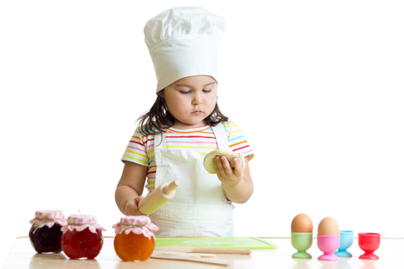 little dough: Child little chef with flour stretching the dough isolated Stock Photo