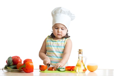 asian children: cheerful kid girl preparing healthy food in the kitchen