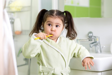 Child kid little girl brushing teeth in bathroom Stock Photo