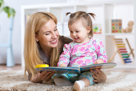 happy mother reading a book to child girl at nursery Stock Photo