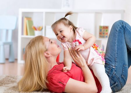 baby playing: young mother with her baby having fun pastime on the floor in nursery Stock Photo