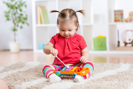 Child little girl plays a musical instrument xylophone sitting on the floor in the nursery