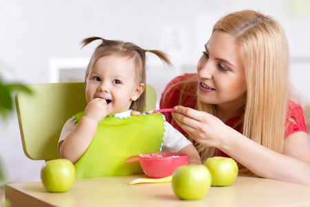 Mother Feeding Baby Girl with Healthy Food Banco de Imagens