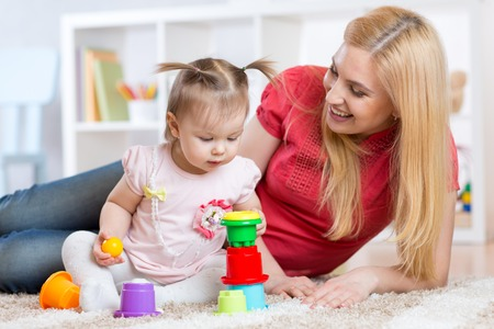 Cute mother and child daughter indoors playing and smiling