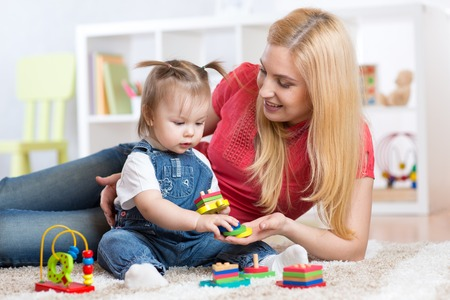 distinguish: Mother teaches her child to distinguish shape and colur plaing with developmental toys.