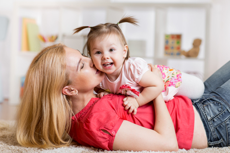 Happy young mother with her baby having fun pastime on the carpet in nursery