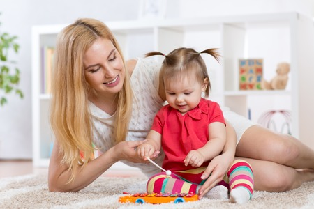 sitter: mother and child play musical instrument in nursery Stock Photo