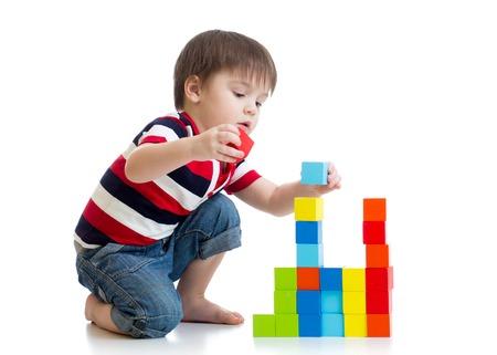 kid enfant garçon jouant avec des cubes de couleur jouets sur le plancher isolé Banque d'images