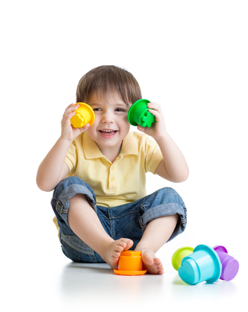 kids toys: Cute child boy playing with toys while sitting on floor, isolated over white