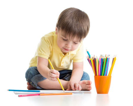 Child little boy drawing with colorful pencils isolated on white