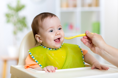 baby food: baby girl eating food on kitchen at home