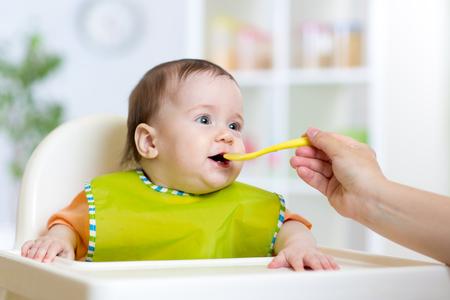 cuchara: Alimentación de la madre a su hija bebé. Niño que se sienta en la silla hich en la cocina.