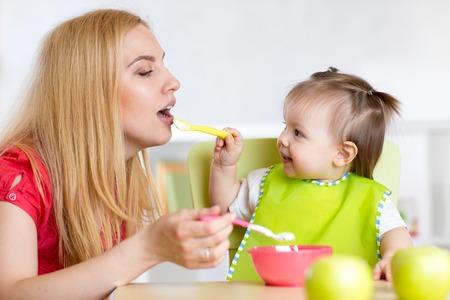 comiendo cereal: Niña y su madre con la comida del bebé alimentación de los demás, se sienta a la mesa en la guardería