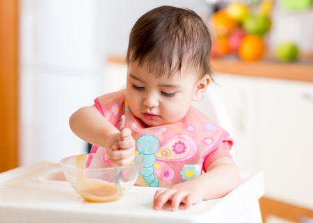 baby child sitting in chair with a spoon and eating food