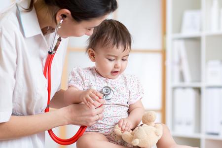 mujer de examen del pediatra del niño del bebé en la oficina Foto de archivo