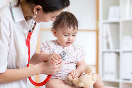 doctor toys: pediatrician woman examining of baby kid in office