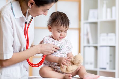 pediatric doctor examining child toddler with stethoscope