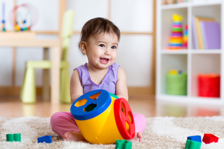 kids playing: Toddler girl playing with a shape sorter toy Stock Photo