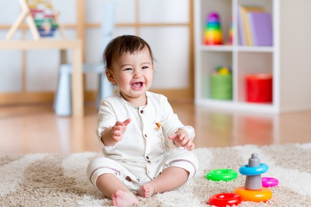 baby nursery: cute cheerful baby playing with colorful toy pyramid at home Stock Photo