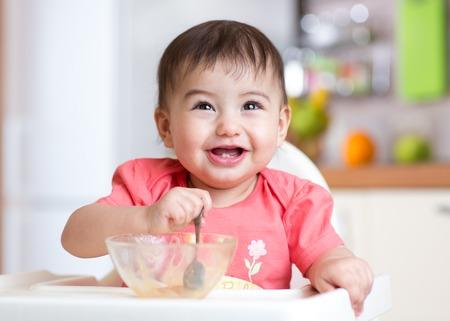 bebes: alegre feliz del niño del bebé de comer comida en sí con una cuchara Foto de archivo