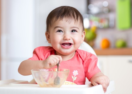 cheerful happy baby child eating food itself with a spoon Stock Photo - 54306996