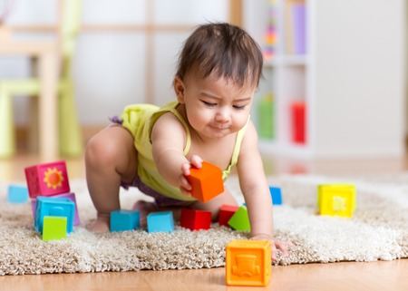 kid toddler playing  wooden toys at home or nursery Archivio Fotografico