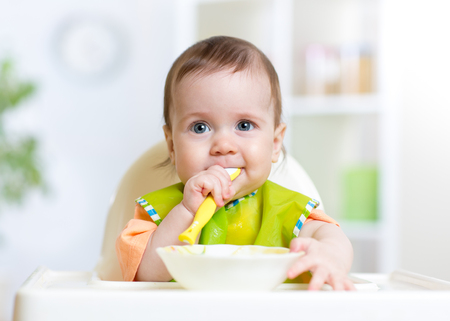 cute baby kid girl eating food on kitchen
