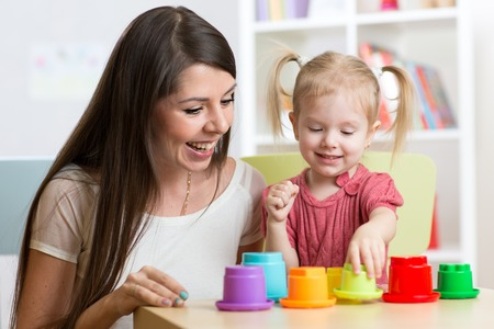 cute mother and her daughter play together indoor