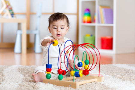 juguetes de madera: muchacha del ni�o que juega con el juguete colorido en la sala de lactancia