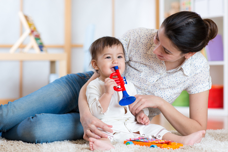 baby and mom playing with musical toys Stock Photo
