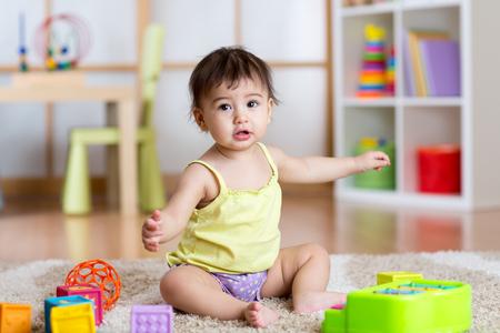 habitacion desordenada: La muchacha del niño que se sienta entre los juguetes en la alfombra en el hogar o cuidado de niños