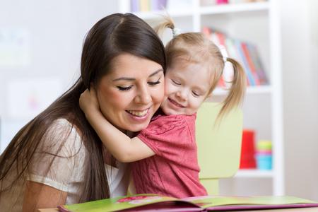 집에서 아이를 껴안고 책을 읽고 해피 어머니