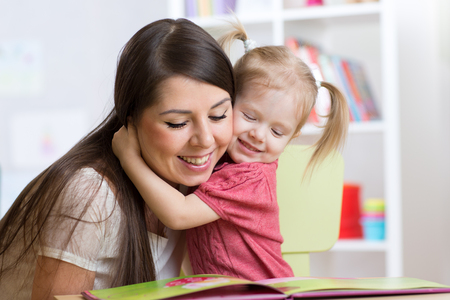 beautiful mom: Happy mother  embracing and reading  a book to kid at home Stock Photo