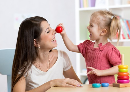 toddler: Smiling mother and little daughter in the nursery, happy time and togetherness