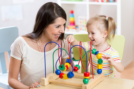 enfant qui joue: child girl and mother playing together with educational toy in nursery