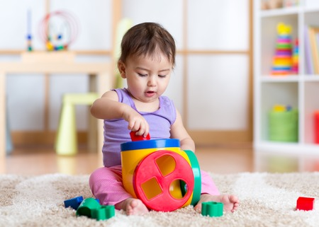 Cute toddler girl playing indoors with sorter toy sitting on soft carpet