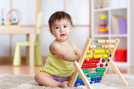 mostradores: muchacha niño que juega con el contador en el vivero Foto de archivo