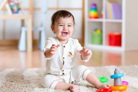 Cute young girl baby playing inside home with colorful toys