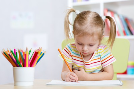 Portrait of lovely girl drawing with colorful pencils Foto de archivo