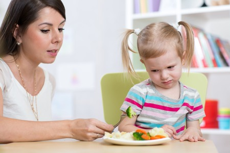 sad little girl: Child girl looks with disgust at healthy vegetables. Mom convinces daughter to eat food.